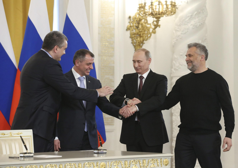 O premiê da Crimeia, Serguei Axionov, o presidente do parlamento da Crimeia, Vladimir Konstantinov, o presidente russo, Vladimir Putin, e o prefeito de Sebastopol, Alexei Chaliy, celebram a anexação da Crimeia e de Sebastopol à Rússia.