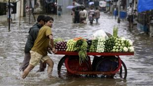 Des vendeurs de légumes poussent leur chariot à travers la ville de Mumbai en Inde, sous les pluies torrentielles de la mousson, le 1er juillet 2008.