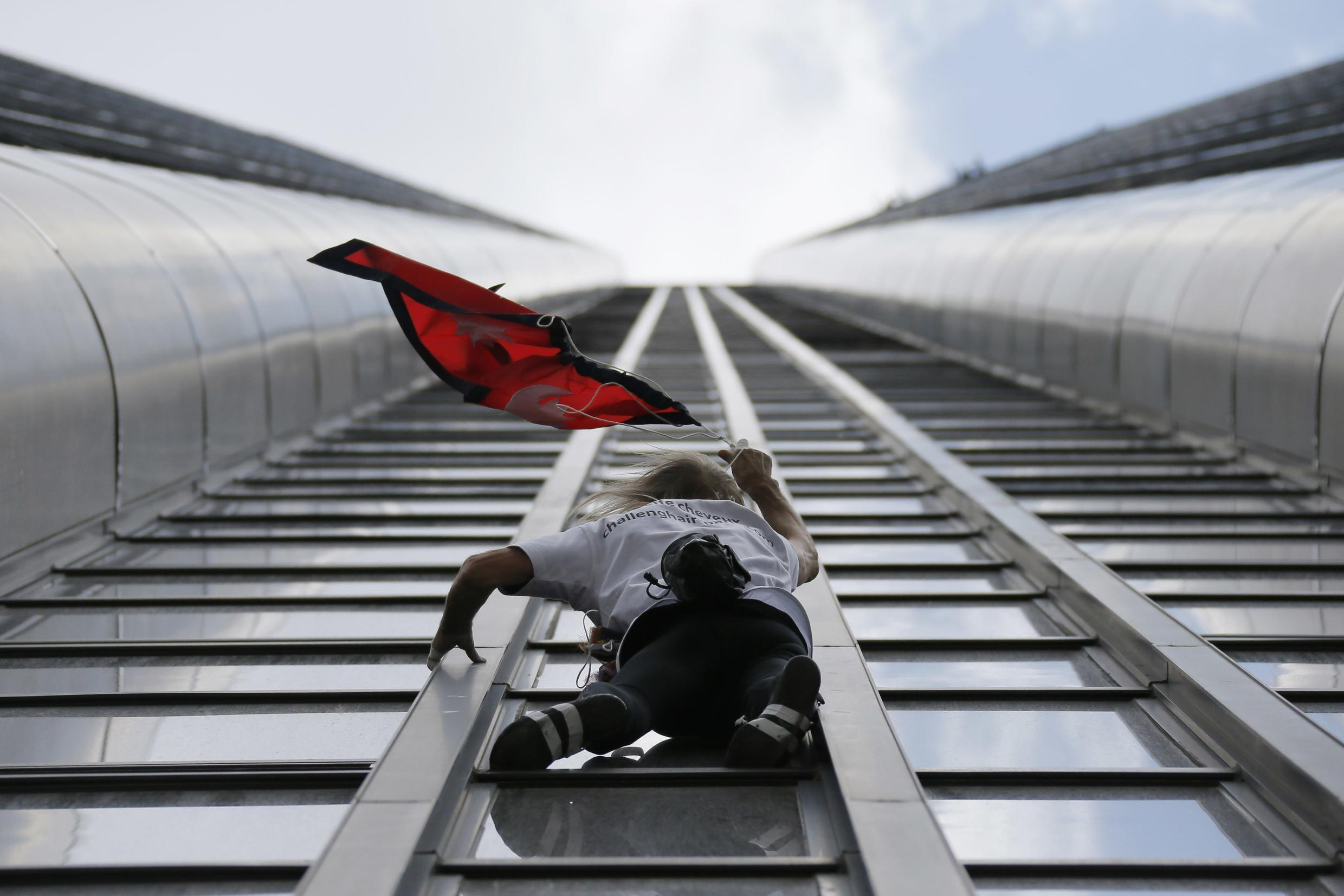 """French climber Alain Robert, also known as """"Spiderman"""", holds the flag of Nepal as he scales the Tour Montparnasse, a 210-metre (689 ft) building in central Paris, France April 28, 2015, to show support for the victims after the earthquake in Nepal."""