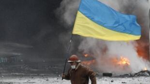 Manifestante pró-europeu anda em meio às chamas na praça da Independência, no centro de Kiev.