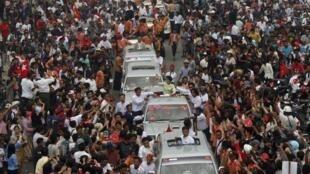 Une foule dense entoure le véhicule d'Aung San Suu Kyi à Mandalay le 3 mars 2012.
