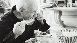 Picasso réalisant Plat avec une arête de poisson en avril 1957 à Cannes. Photographie : David Douglas Duncan.