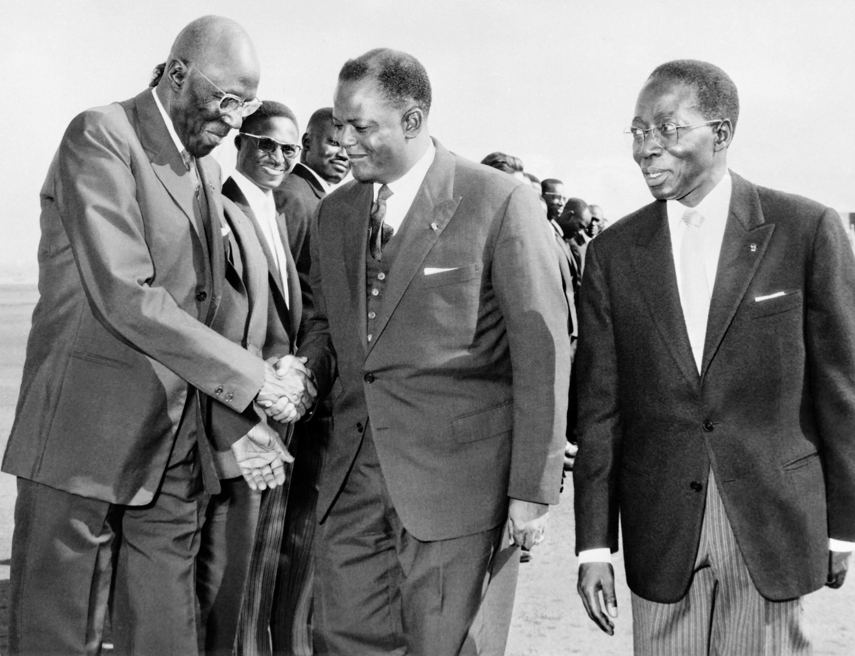 Le président du Parlement sénégalais Lamine Guèye (à gauche) serre la main du président béninois Hubert Maga (au centre), au côté de son homologue sénégalais Léopold Sédar Senghor, le 6 mai 1963 au Sénégal.