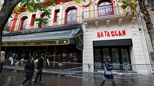 People walk past the Bataclan Cafe and the new facade of the Bataclan concert hall almost one year after a series of attacks at several sites in Paris.