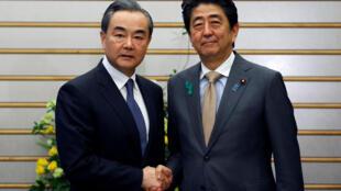Le ministre chinois des Affaires étrangères (G) et le Premier ministre japonais, à Tokyo, le 16 avril 2018.