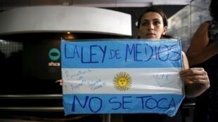 Una manifestante repudia el despido de Martín Sabbatella, ex jefe del ente regulador de los medios en Argentina.