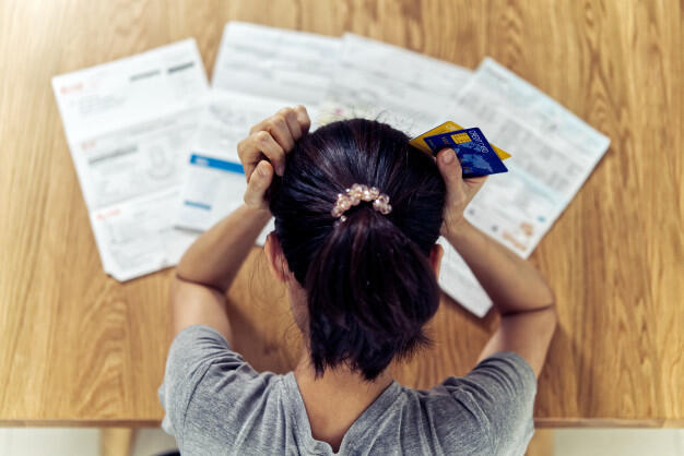top-view-stressed-young-sitting-asian-woman-hands-holding-head-worry-about-find-money-pay-credit-card-debt-all-loan-bills_78212-236