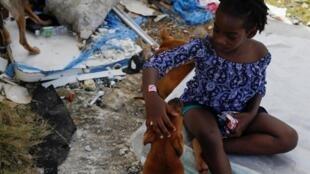 Une jeune fille caresse son chien après que l'ouragan Dorian ait frappé les îles Abaco à Spring City, aux Bahamas, le 11 septembre 2019.