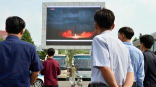 В Пхеньяне смотрят отчет о запуске баллистической ракеты на большом экране, 30 августа 2017 г.