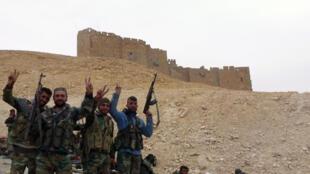 Des forces pro-gouvernementales syriennes posent sous la citadelle de Palmyre, une ville qui fut longtemps occupée par le groupe Etat islamique.