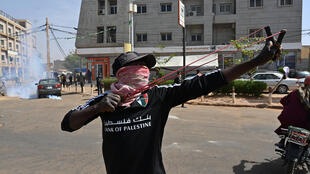 An opposition demonstrator uses a slingshot to launch stones at police in Niamey.