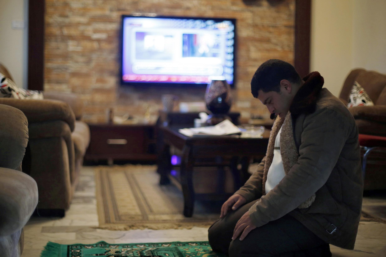 Jawad al-Kasaesbeh, irmão do piloto jordaniano Muath, cujo avião caiu na Síria no dia 24 de dezembro de 2014, reza enquanto espera notícias. O governo sírio desmentiu nesta sexta-feira que o avião tenha sido abatido pelo Grupo Estado Islâmico.