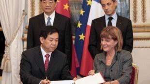 Anne Lauvergeon, présidente du directoire d'Areva (d) et He Yu, président du groupe chinois CGNPC (g), signent un important contrat, à Paris, le 4 novembre 2010.