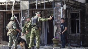 La police tente d'éloigner les piétons du lieu où s'est produit le triple attentat à Grozny.