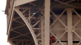 Bombeiros durante o resgate do homem que ficou pendurado durante mais de seis horas na torre Eiffel