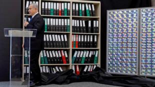 """بنیامین نتانیاهو، نخست وزیر اسرائیل در کنفرانس خبری دوشنبه ٣٠ آوریل ٢٠۱٨ در تلآویو، شمار فراوانی کلاسور  و همچنین تابلوئی که بر روی آن ١۵٦ """"سی.دی"""" نصب شده بود را به عنوان اسناد بدست آمده یاد کرد و ایران را به پیگیری یک برنامۀ اتمی مخفیانه متهم کرد."""