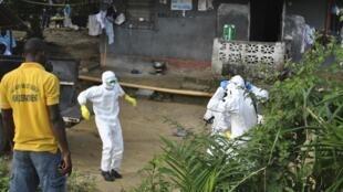 Personnel de santé en vêtements de protection dans un centre de soin à la frontière entre le Liberia et la Sierra Leone, le 5 novembre 2014.