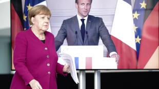 La primera ministra alemana Angela Merkel (I) en Berlín y el presidente francese Emmanuel Macron desde París en una pantalla durante la rueda de prensa conjunta que dieron a través de videoconferencia, el 18 de mayo de 2020