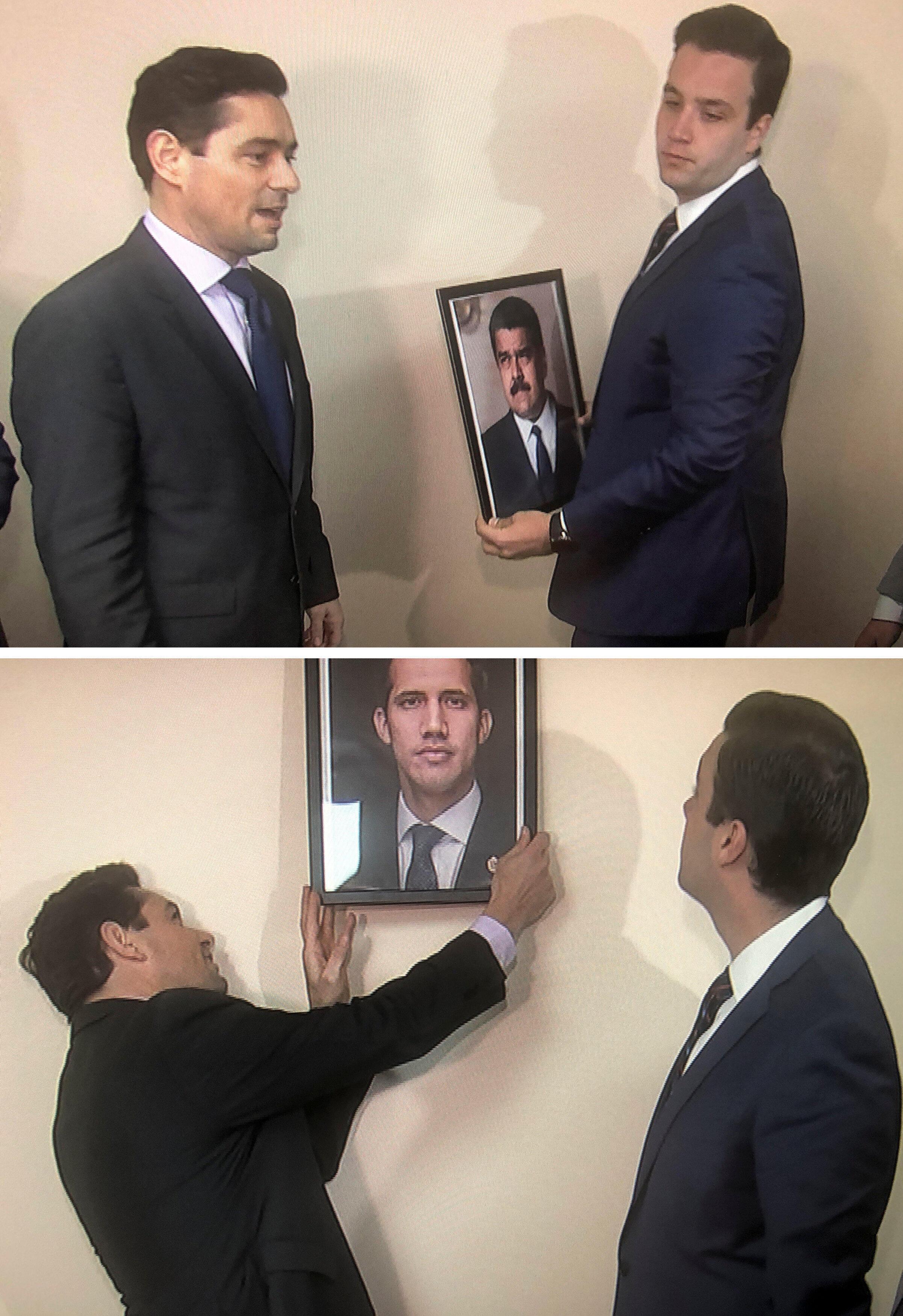 Carlos Vecchio (à gauche), l'envoyé aux États-Unis du chef de l'opposition vénézuélienne remplace la photo de Nicolas Maduro par celle Juan Guaido après avoir pris le contrôle d'un bâtiment à Washington, le 19 mars 2019.