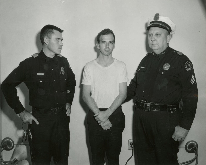Lee Harvey Oswald (G), người bị cáo buộc sát hại tổng thống Mỹ JF. Kennedy, bị bắt tại Dallas. Ảnh chụp ngày 22/11/1963.