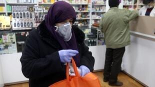شماری از ایرانیان، چنانکه تصویر بانوئی که برای خرید به داروخانه مراجعه کرده نشان میدهد، برای پیشگیری از ابتلا به بیماری کوید ١٩، هنگام خروج از خانه از ماسک و دستکش استفاده میکنند - ٦ اسفند ١٣٩٨