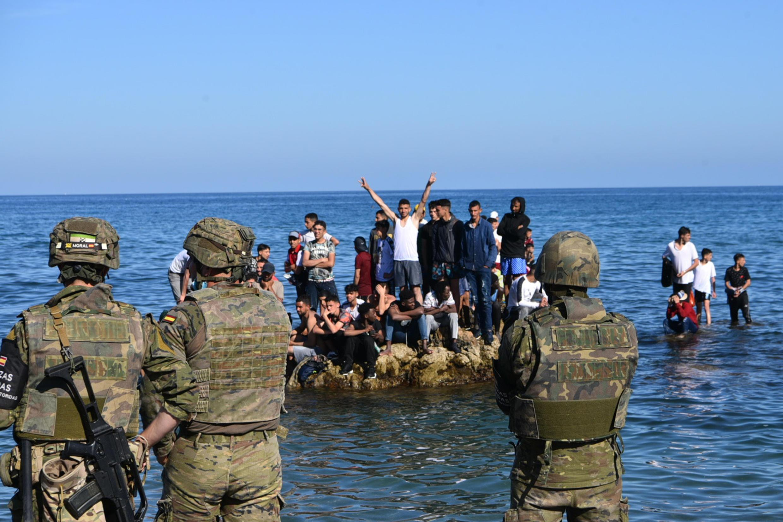 Soldados españoles observan a un grupo de migrantes que permanecen en las rocas situadas frente a una playa de Ceuta, el 18 de mayo de 2021 en la ciudad española al norte de África