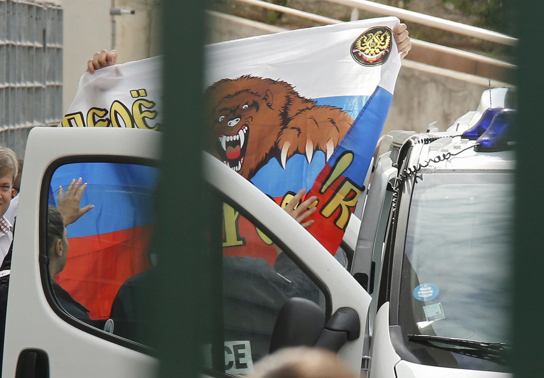 Задержанный российский фанат показывает флаг при переводе из центра временного содержания в Марселя в Ниццу, 18 июня 2016 г.