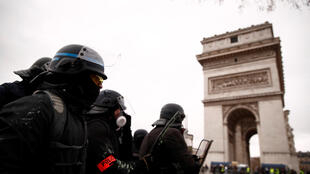 Riot police stand guard during a demonstration by the Yellow Vests movement near the Arc de Triomphe in Paris, 12 January 2019.