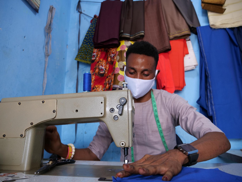 Emmanuel Ojo fabrique des masques dans son atelier de couture.
