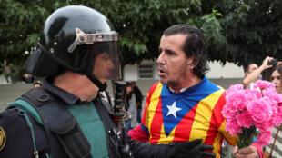 Un homme vêtu d'un t-shirt aux couleurs du drapeau catalan face à un policier dans une rue de Sant Julia de Ramis, le 1er octobre 2017, le jour du référendum interdit.