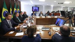 El presidente brasileño Jair Bolsonaro y algunos miembros de su gabinete escuchan al presidente estadounidense Joe Biden (en pantalla), durante la cumbre de líderes mundiales sobre el clima, en el Palacio de Planalto, en Brasilia, el 22 de abril de 2021
