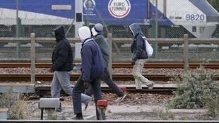 Des migrants longent les trains en départ vers le Royaume-Uni à Calais, en France.