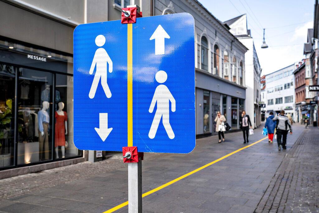 A faixa amarela e a sinalização ajudam as pessoas a manter a distância social nas ruas de Aalborg, Dinamarca, em maio de 2020.