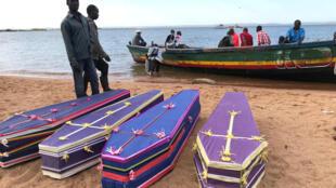 Voluntários arrumam caixões com os corpos dos passageiros que estavam no balsa MV Nyerere que naufragou no lago Vitória, 22 de setembro 2018