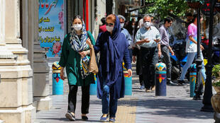 Pedestrians wearing protective masks due to the coronavirus walk past shops in the Iranian capital Tehran