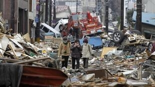 People among the ruins of the destroyed residential part of Kamaishi, more than a week after theMarch 2011 earthquake and tsunami.