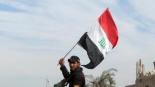 Un miembro de las fuerzas de seguridad iraquíes alza una bandera de Irak en la ciudad de Ramadi retomada este lunes 28 de diciembre de 2015 a los yihadistas del grupo Estado Islámico.