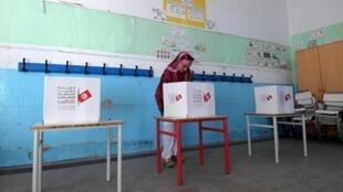 Une électrice dépose son bulletin dans l'urne pour les législatives, le 6 octobre 2019.
