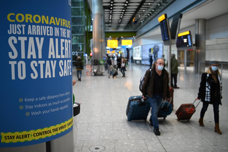 Advertencias sanitarias del coronavirus se observan en la sala de arribos del aeropuerto Heathrow en el oeste de Londres, el 15 de enero de 2021