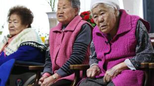"""Бывшие """"женщины для утешения"""" смотрят выпуск новостей, Гванджу, Южная Корея 28 декабря 2015 г."""