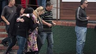 Miners' family members comfort each other after visiting Pike River coalmine to see rescue preparations