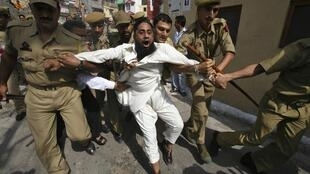 An anti-Delhi-rule protester is arrested in Kashmir