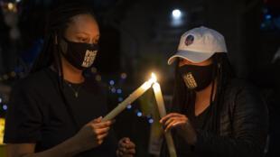 Dos mujeres encienden unas velas durante una vigila por Daunte Wright el 17 de abril de 2021 en Brooklyn Center (EEUU)