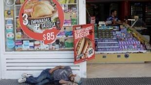 Un hombre duerme frente a una tienda en Buenos Aires, Argentina, el 25 de octubre de 2019.
