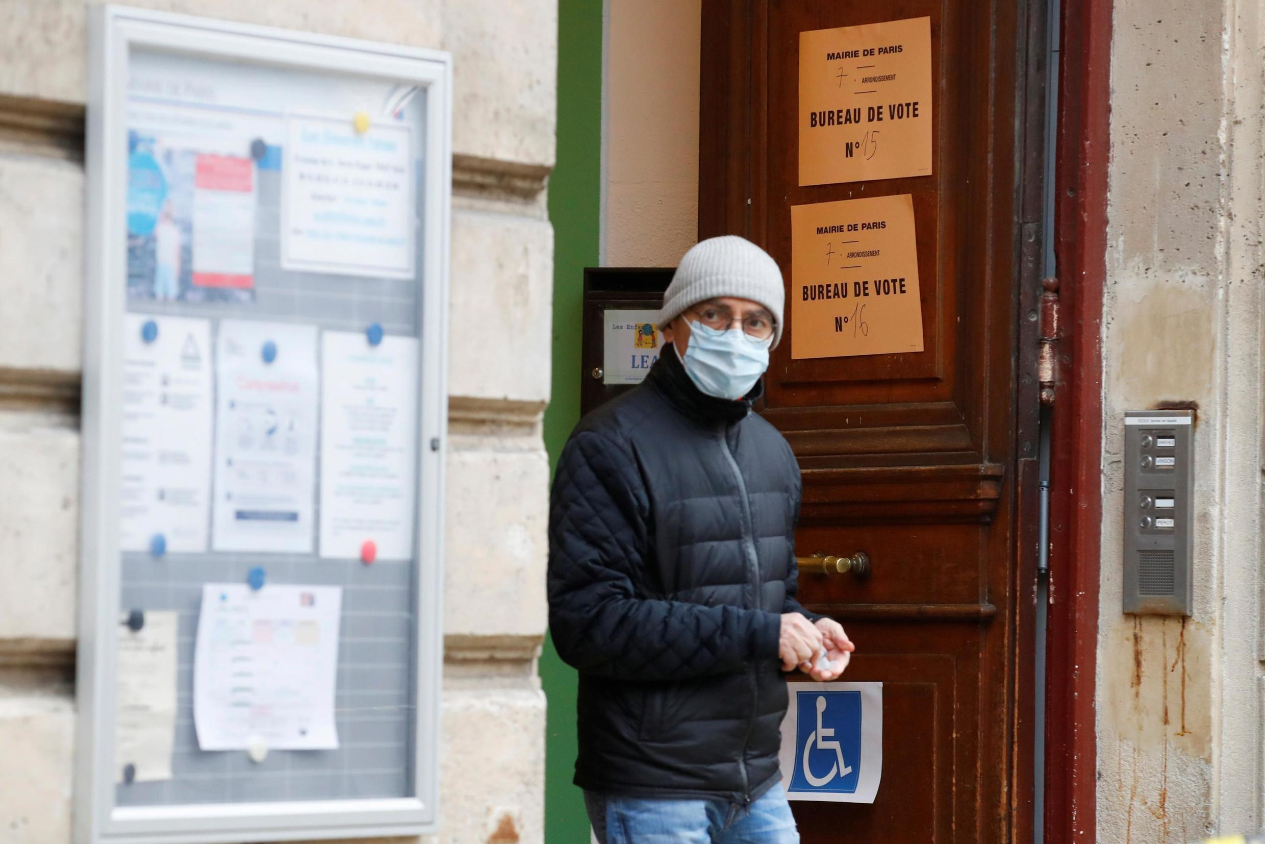 A man leaves a voting booth in Paris amid strict hygienic measures taken in the wake of the coronavirus epidemic