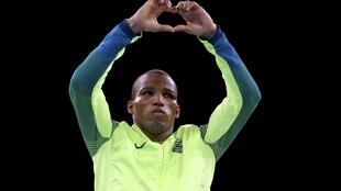 Robson Conceição, no pódio da Rio 2016 faz o gesto do coração com as mãos.