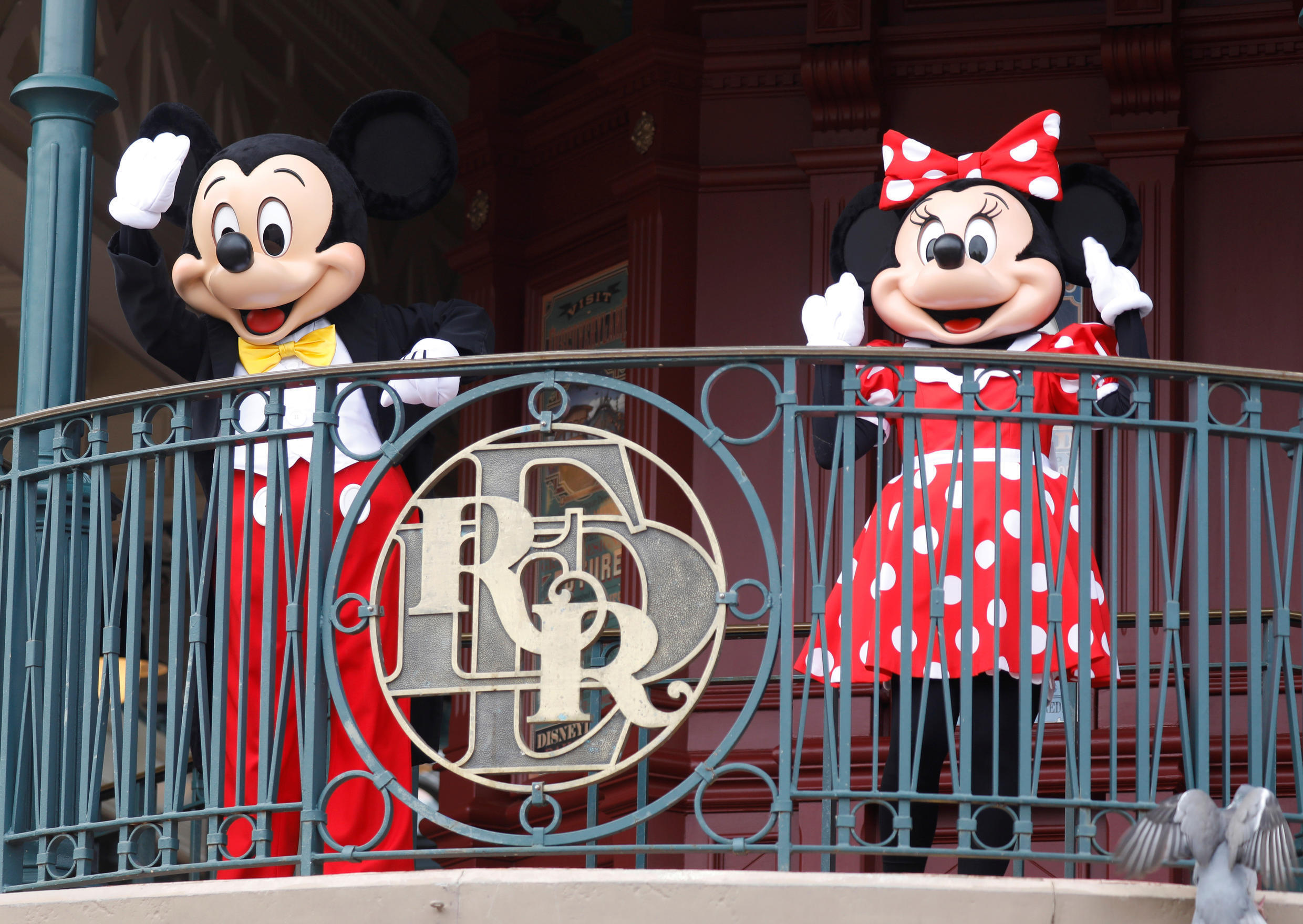 Disney characters Mickey and Minnie Mouse welcome visitors to Disneyland Paris as the theme park reopens its doors after a four-month shutdown.