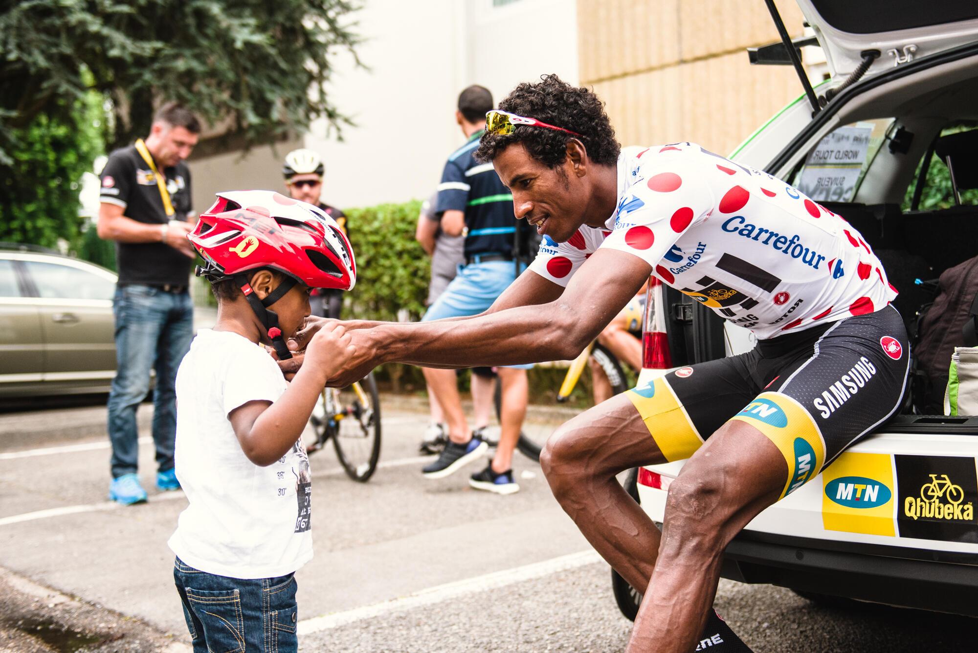 L'Erythréen Daniel Teklehaimanot, maillot à pois sur les épaules, avec un petit fan sur le Tour de France 2015.