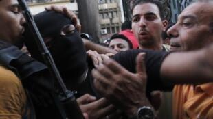 Membro das forças especiais egípcias tenta circular entre apoiadores do governo interino diante da mesquita al-Fath