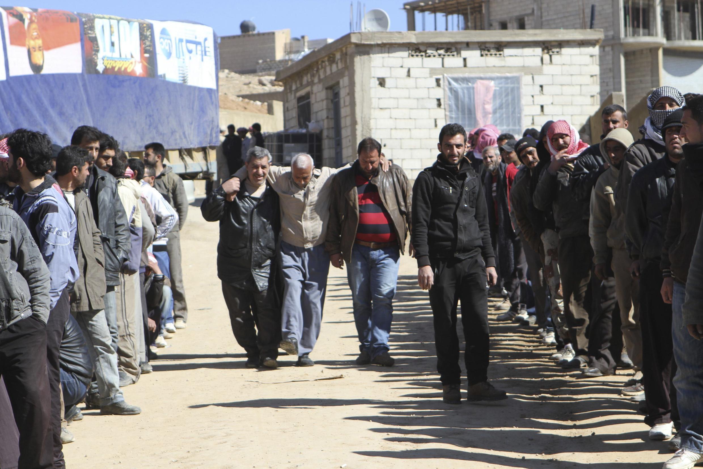 Des réfugiés syriens de la région du Qalamoun, où ils recoivent une aide humanitaire, près de Ersal, le 18 février 2014.